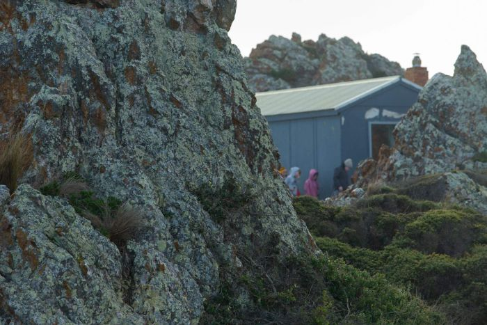 The visiting kids walk around a hut, tucked between large coastal rocks