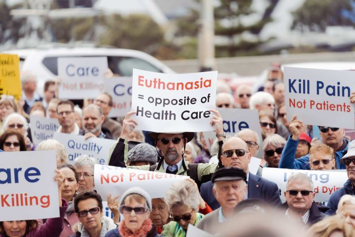 A crowd of people holding up placards protest at a rally outside WA Parliament House against voluntary euthanasia.