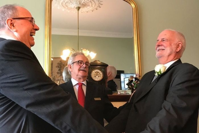 Father Rob Whalley and Father John Davis in black wedding suits, facing each other holding hands and smiling.