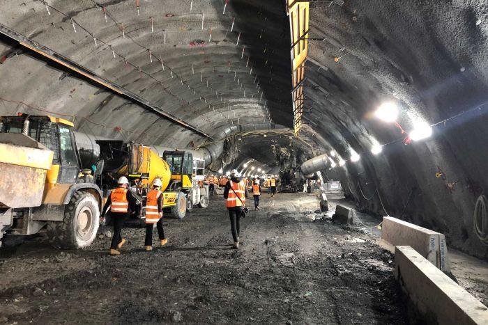 Workers pictured walking away from the camera next to machinery in a huge underground tunnel.