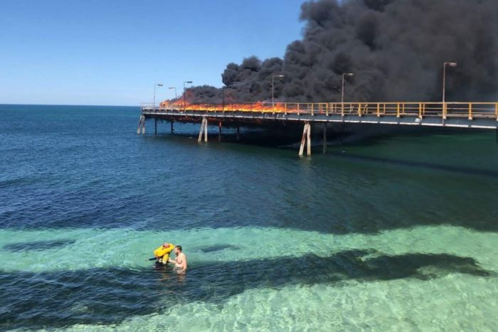 Two men in the sea with a jetty in flames behind