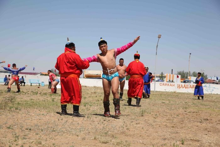 Mongolian wrestlers raise their arms in a ceremony dance before competing.