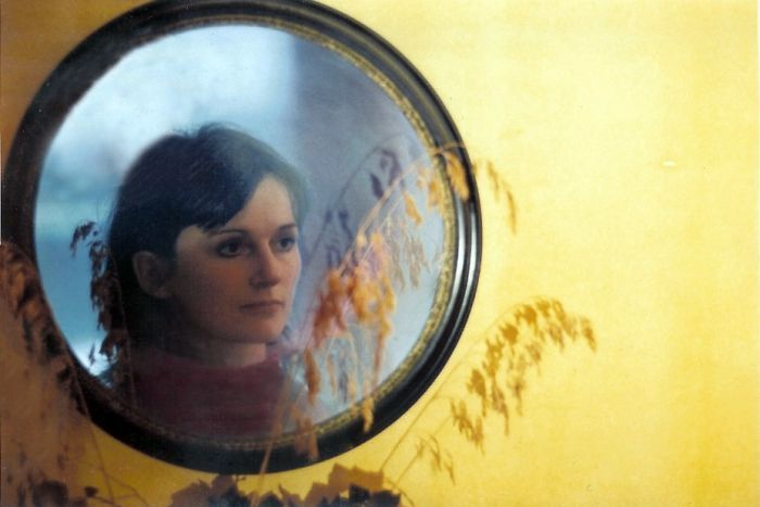 A young Amanda Feilding looks into a circle mirror hung on a yellow wall.