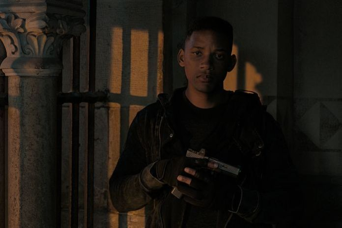 Will Smith stands in the shadows wearing a black outfit and holding a pistol to his chest.