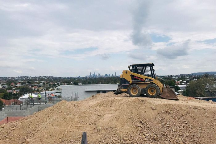 Excavator at housing construction site at Wavell Heights with Brisbane CBD in background.