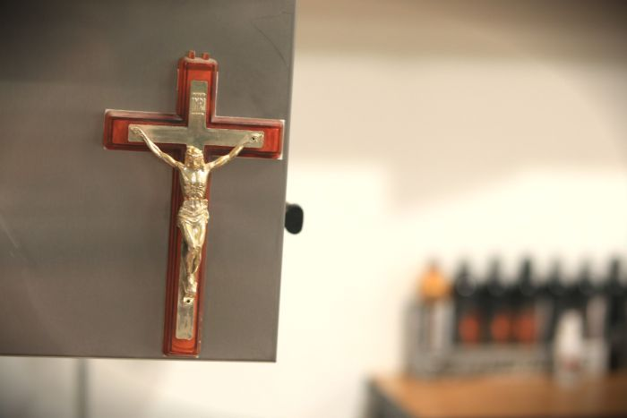 A crucifix hanging in the laser tattoo removal studio.