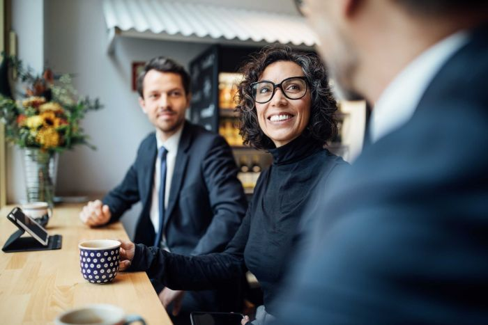 Two men and a woman sit at a table in a work environment conversing over coffee.