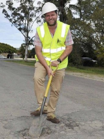 The Byron Shire mayor Simon Richardson wearing a high-vis vest and holding a shovel in a pothole on a sealed road