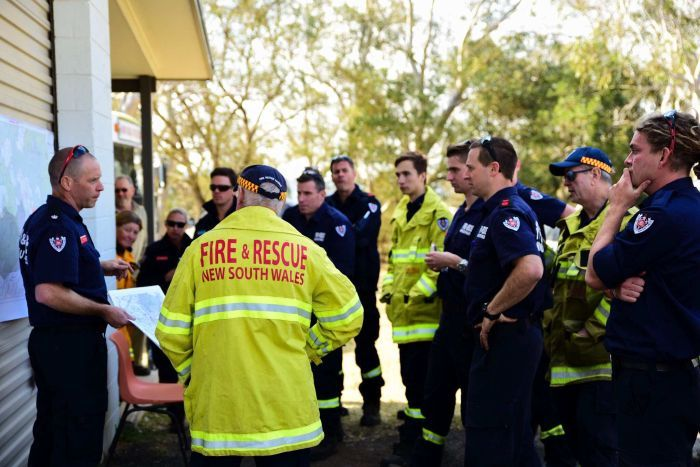 Firefighters stand around listening to a briefing, the closest to camera is wearing a bright florescent jacket.
