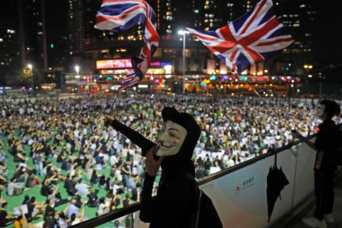 Anti-government protesters carry British flags as a man wears a white mask in front of the crowd.
