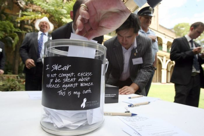 A man puts an oath into a swear jar vowing not to be silent against domestic violence.