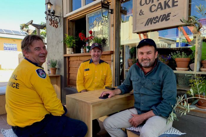 Three men sit at a cafe table. Two are in yellow RFS shirts and the other is in a blue long sleeve shirt.