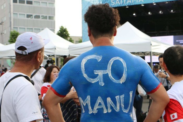 "A male Japanese rugby union supporter wearing body painted samoa jersey with ""Go Manu"" written on his back."