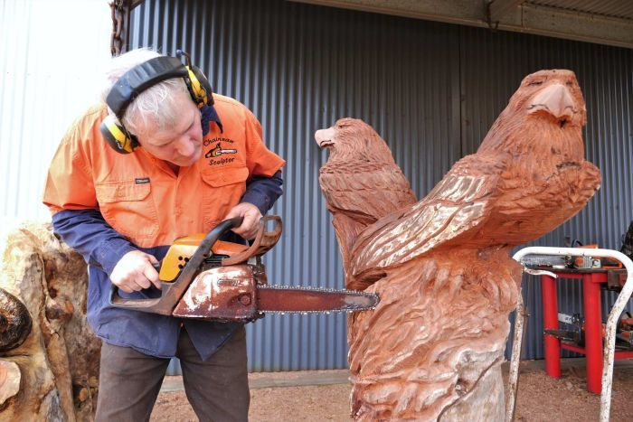 Darrel Radcliffe carves a sculpture of a pair of eagles with a chainsaw.