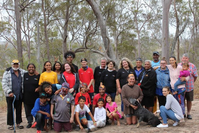 A group of people, both Indigenous and non-Indigenous, and of all ages, stand and kneel, smiling, in a bush setting.