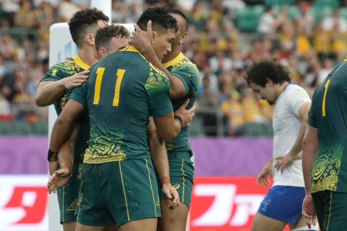 A Wallabies player is hugged by his teammates as he holds the ball after scoring a try at the Rugby World Cup.