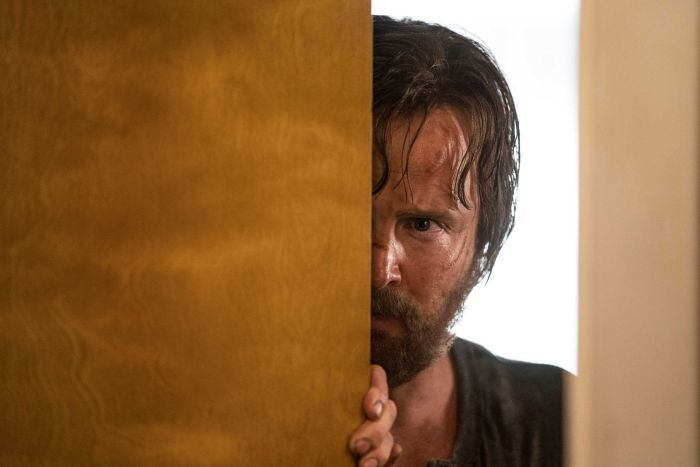 Jesse Pinkman, with a dirty face and ragged hair, peaks past a door through a doorway