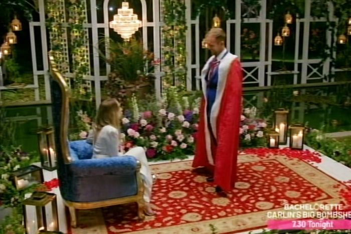 Jess Glasgow dressed in red regal robes standing in front of The Bachelorette Angie Kent sitting in a blue throne.