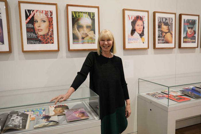 A distinguished woman leans against a glass case filled with magazine covers.