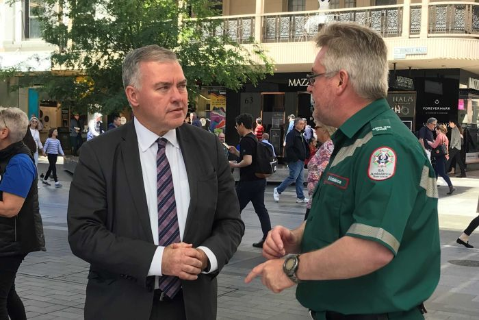 Health Minister Stephen Wade talking to an ambulance officer.