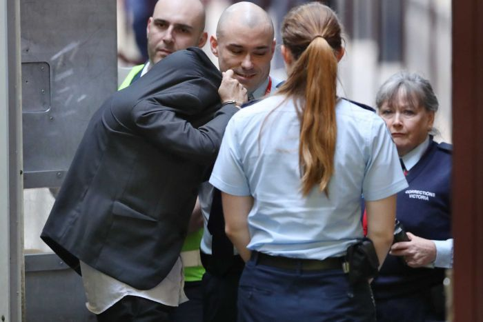 A man with his face hidden by his jacket is escorted into court by security guards.