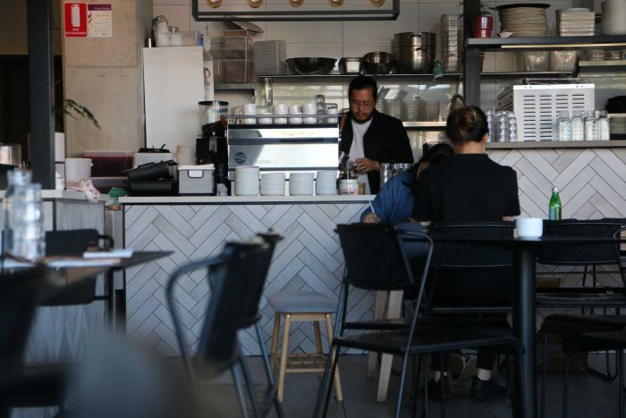 A man pouring a coffee behind a desk in a cafe