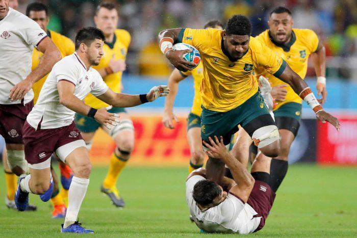 A Wallabies player runs the ball at a Georgian opponent at the Rugby World Cup.