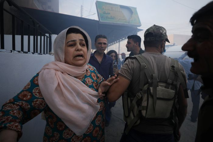 A woman reacts at the site of a car bomb blast in Qamishli, Syria.