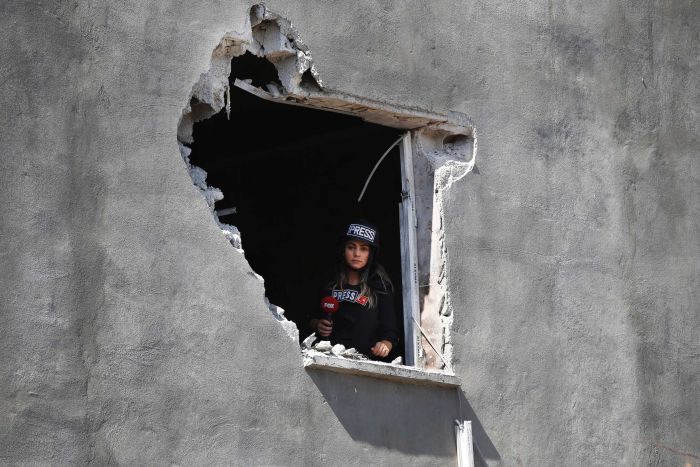 A female journalist looks out of an hole on a house damaged by mortar fire.
