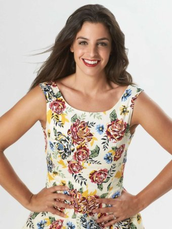 A pretty young woman in a floral dress smiles at the camera.