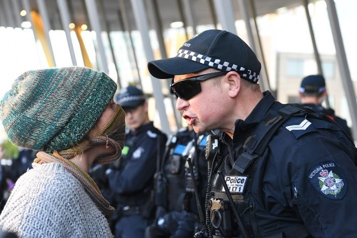 A police officer and protester stand up close, face to face, with the officer shouting at the protester.