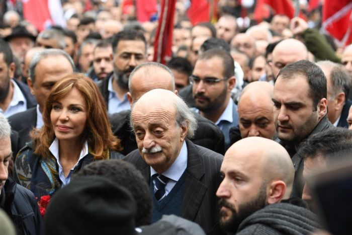 Walid Jumblatt walks in a crowd of supporters. He is bald and has a moustache.