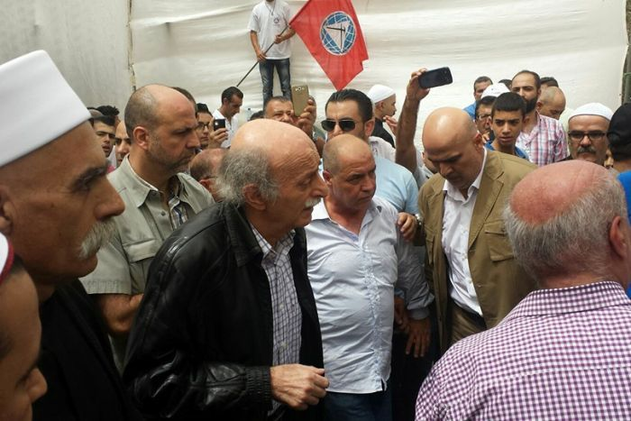 Walid Jumblat walks with supporters, a flag of his party is in the background