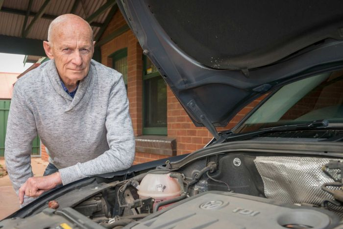 A man leans over the engine of his car.