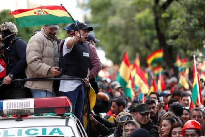 Luis Fernando Camacho stands at the back of a police vehicle waving the Bolivian flag.