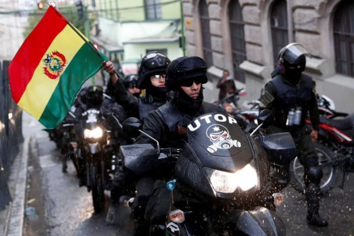 Policemen drive motorcycles. A Bolivian flag is shaken.