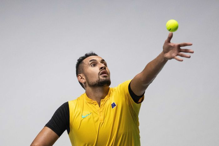 Nick Kyrgios throws the ball up as he prepares to serve.