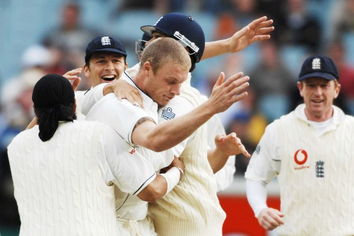 Andrew Flintoff holds his arms in the air with his head bowed as he is mobbed by teammates during the MCG Test.