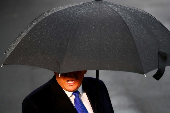On a rainy day, Donald Trump's mouth and body are seen under a black umbrella.