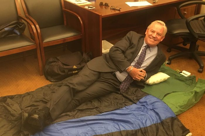 A man in a suit lies down on a swag in a parliamentary office