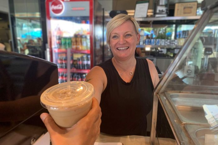 Ms Norton hands an iced latte to a customer.