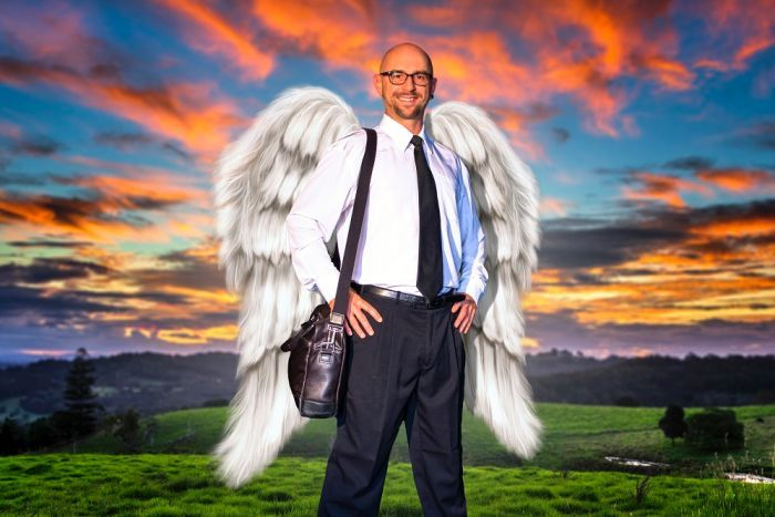 A stylised image of a man with big angel wings standing in green field.
