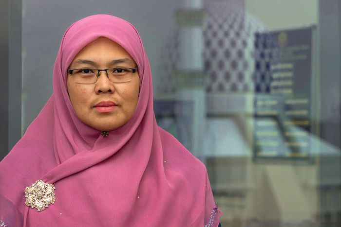 A woman wearing a pink hijab poses for a photo with a serious expression on her face.