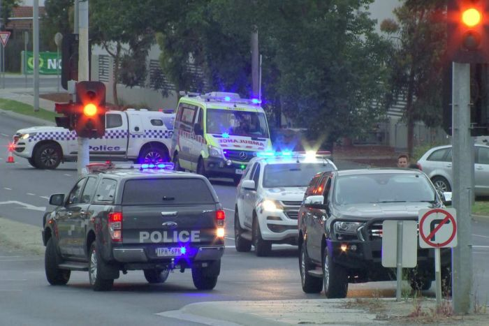 Several police cars and an ambulance at the scene of a car crash in the early morning.