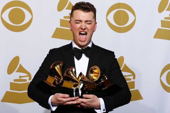 Pop star Sam Smith makes a funny face for the cameras while holding four Grammy awards in front of a media backdrop