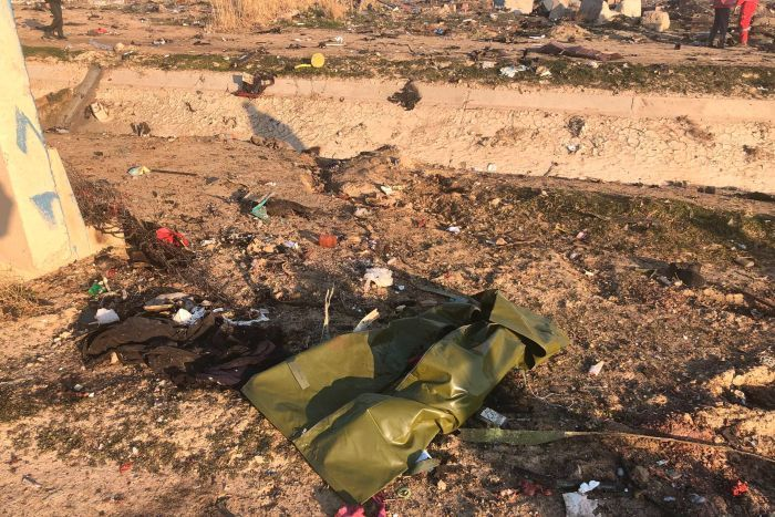 A bag and a piece of clothing along with many other items of debris lay on the floor. The feet of two people are seen on the far right.