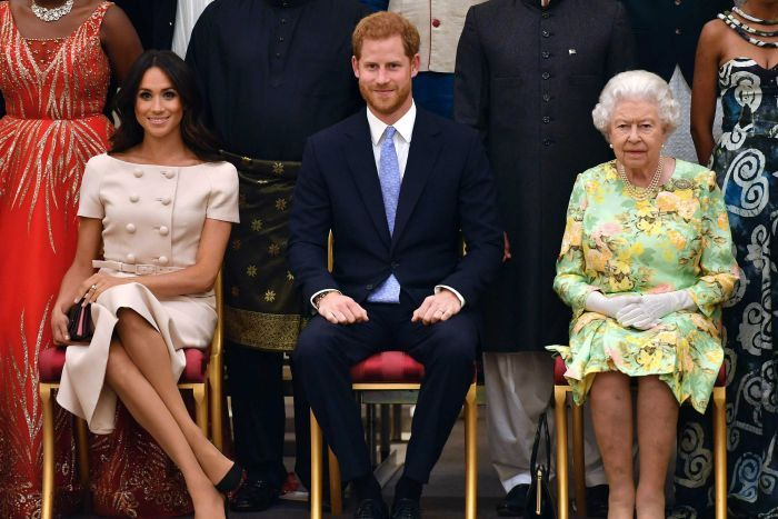 Meghan, the Duchess of Sussex, Prince Harry and Queen Elizabeth sit in chairs in front of other people.