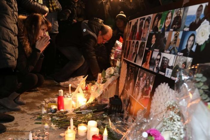 The mourners gather to pay homage with candles and photos of the victims of the Ukrainian passenger plane that crashed in Iran.
