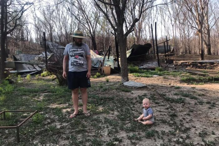 A man stands in front of a burnt out house with his toddler on the ground