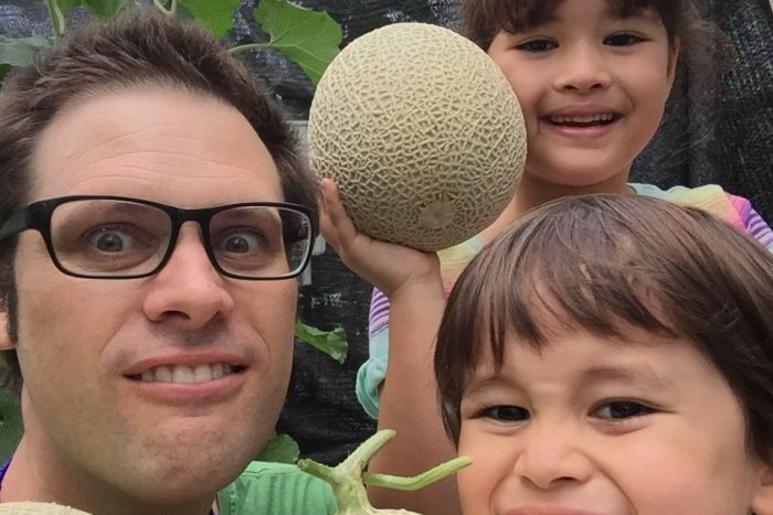 Australian journalist Scott McIntytre, with glasses, looks at the camera with his two children. They are holding rock melons.